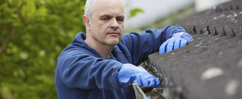 Mann rengjør takrenne
