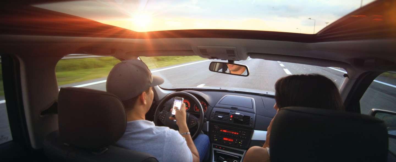 Ung person kjører bil og sjekker mobilen