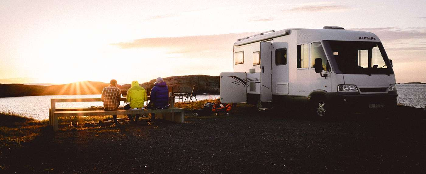 Bobil som står parkert langs en fjord. Foto.