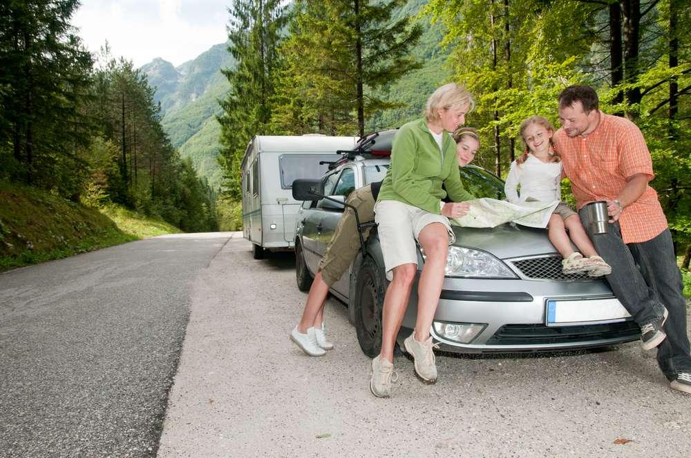 Familie med campingvogn forsikret i Frende sjekker kartet på ferieturen