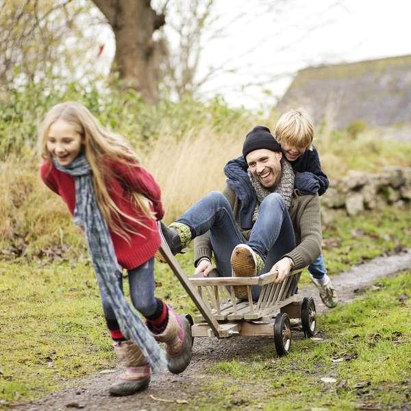 Liv- og helseforsikring i Frende - sønn og datter leker med pappa sittende i en trillebår