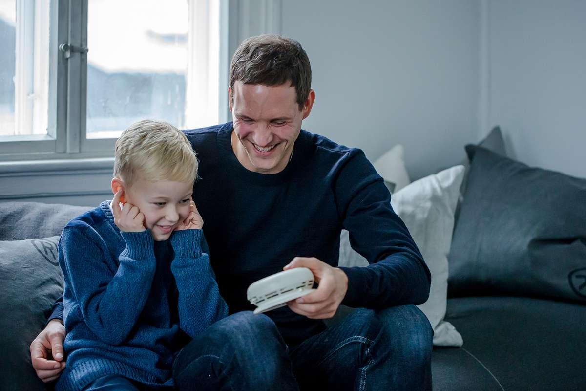 Sønn og far sjekker batteriet i røykvarsleren