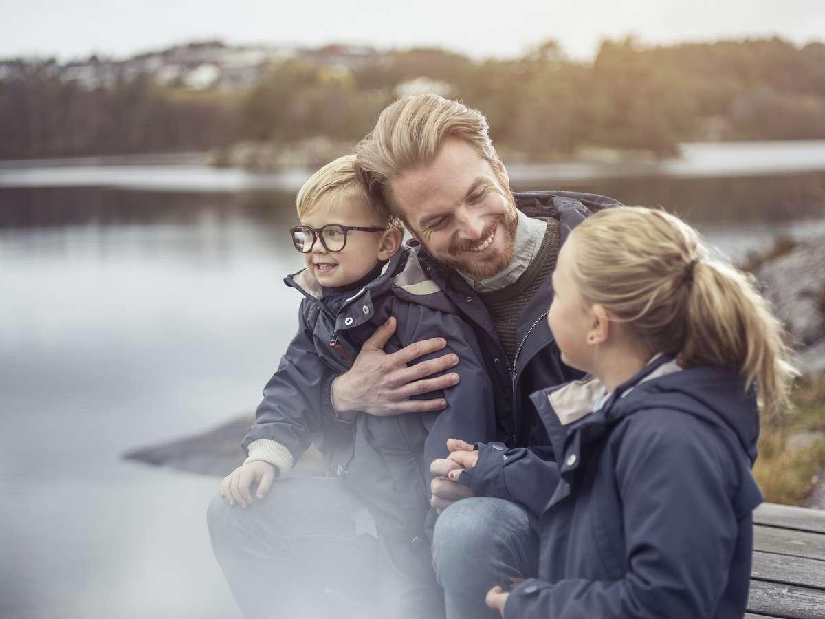 Smilende mann med to barn