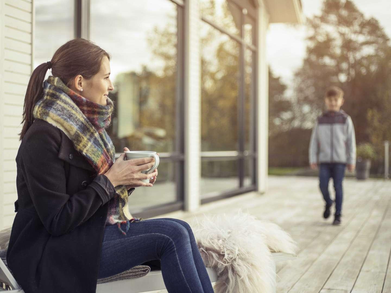 Kvinne på terasse med sønnen sin og en kopp kaffe