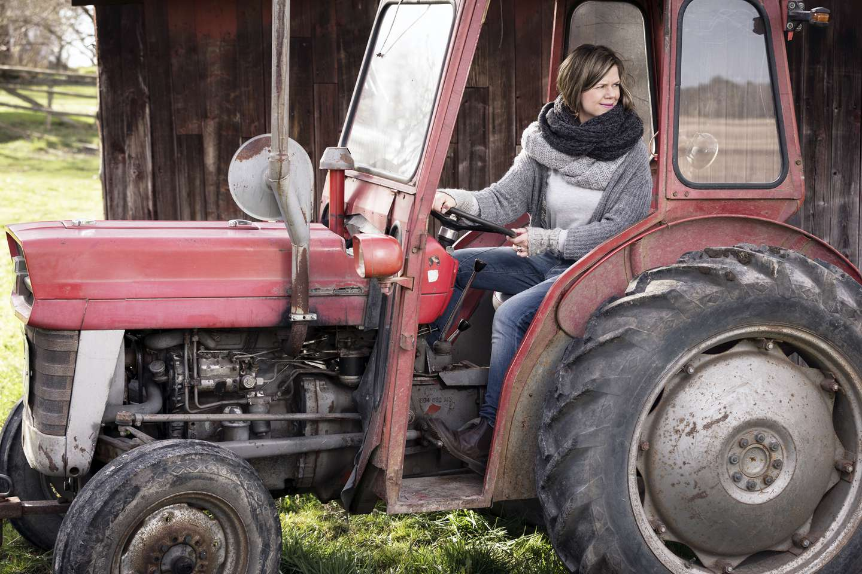 Dame sitter i en traktor som er forsikret i Frende