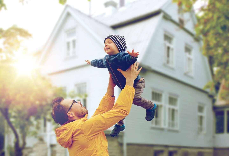 Mann og barn leker i hagen utenfor hus