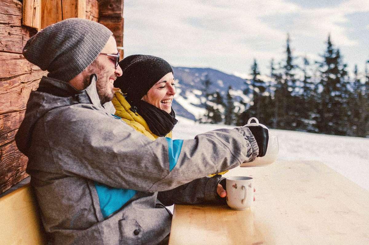 Par slapper av på en benk utenfor hytten