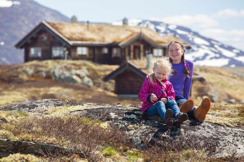 To jenter utenfor hytte på høstfjellet