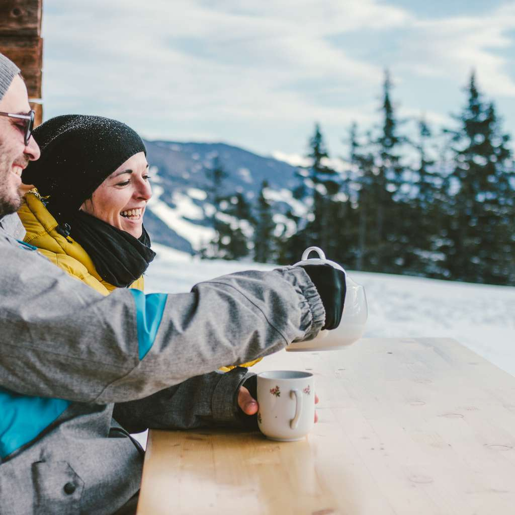 Par slapper av på en benk utenfor hytten som er forsikret i Frende