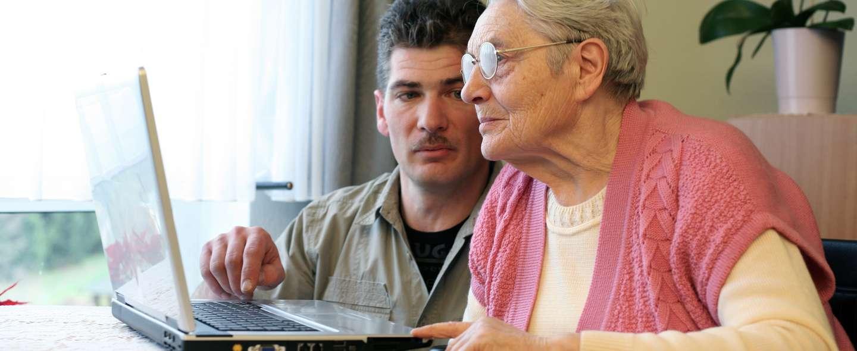 Mann hjelper eldre kvinne med bruk av PC