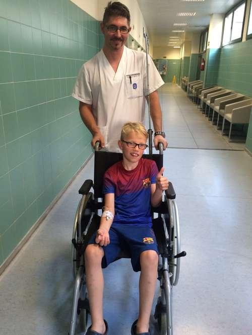 Elias gir tommel opp fra rullestolen på sykehuset i Spania.