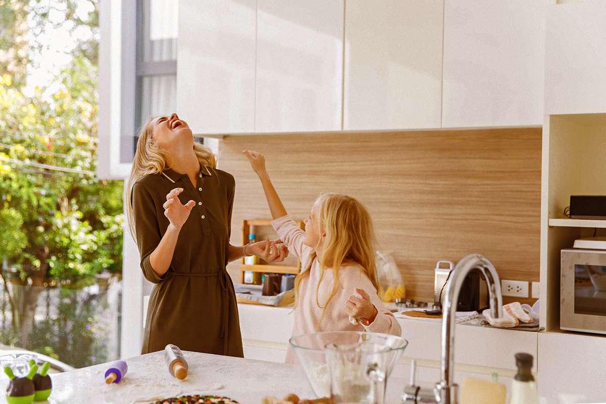 Mor og datter leker på kjøkkenet
