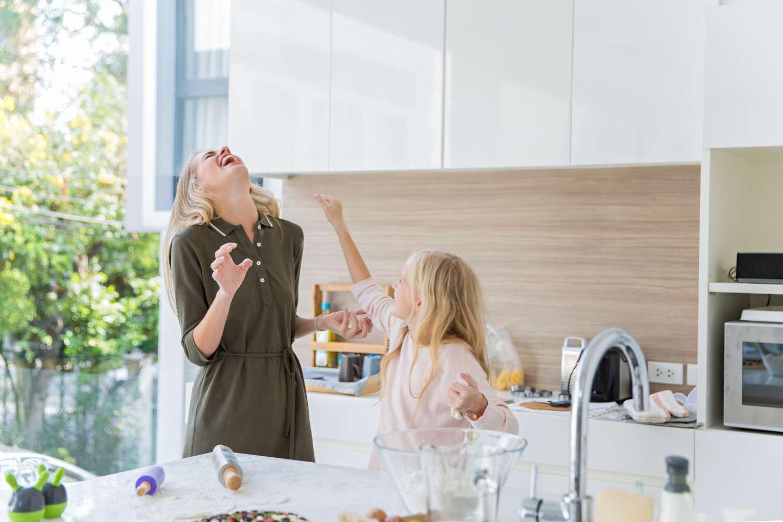 Hus- og innboforsikring i Frende - mor og datter leker på kjøkkenet
