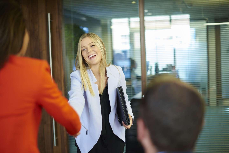Kvinne ønskes velkommen til jobbintervju