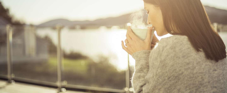Dame drikker kaffe på terrasse