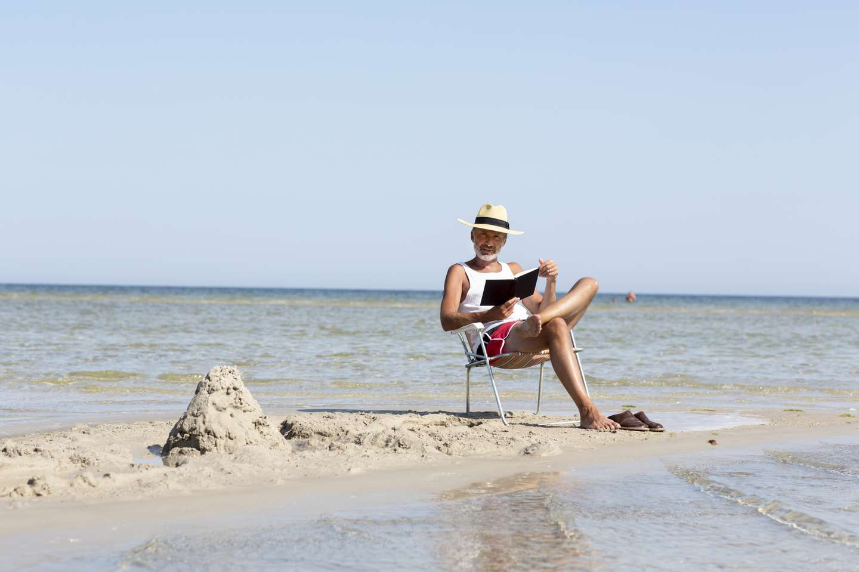 Mann i solstol leser bok på stranden.jpg