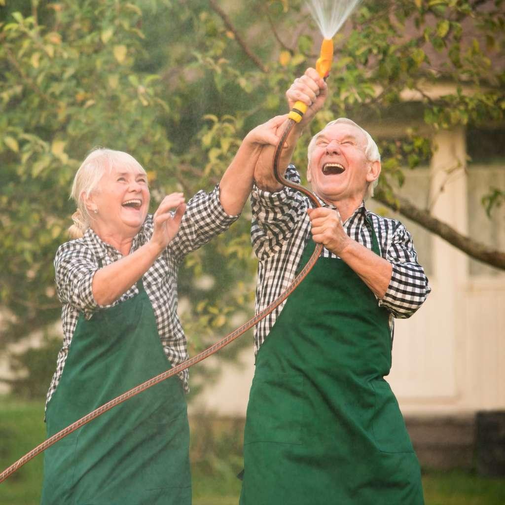 Eldre par i hagen med spyleslange