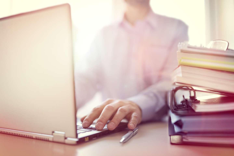 Person med permer foran PC.jpg