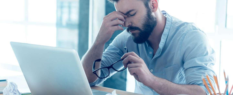 Fortvilet mann foran PC
