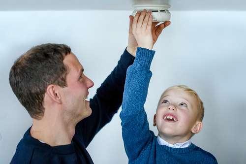 Far og sønn bytter batteri i røykvarsleren