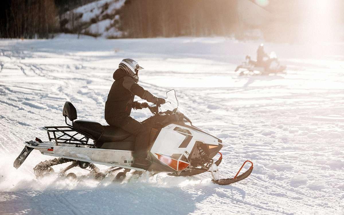 Person kjører snøscooter. Foto.