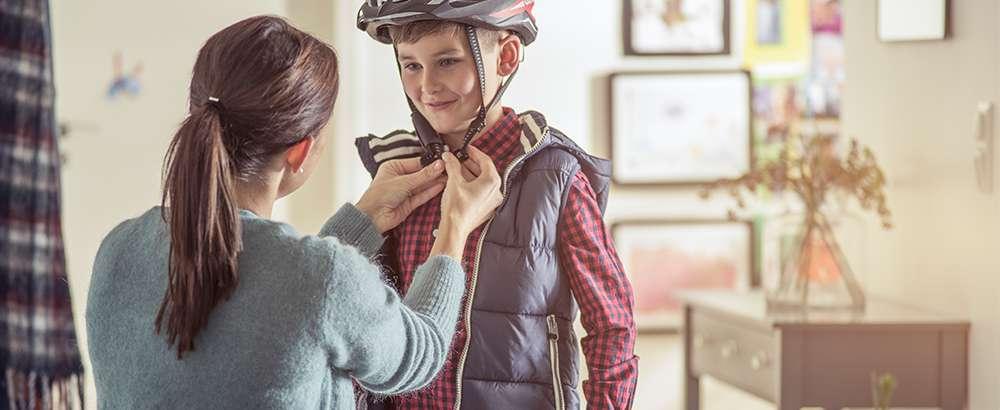 Mor tar på sykkelhjelm på sin sønn