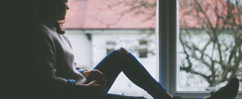 Ung kvinne sitter i vinduskarmen og ser ut
