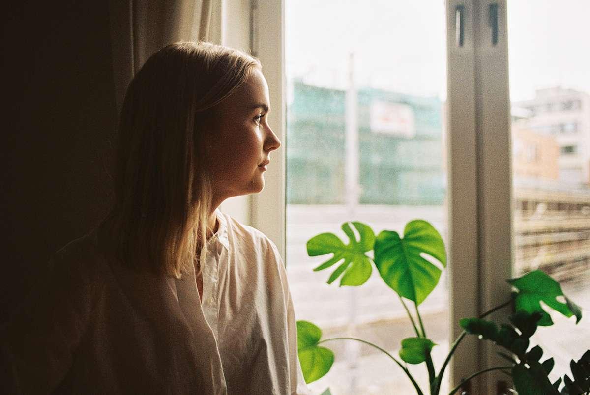Kvinne som ser ut vindu. Foto.