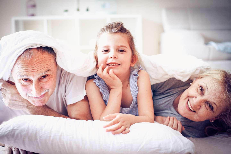Smilende besteforeldre og barnebarn