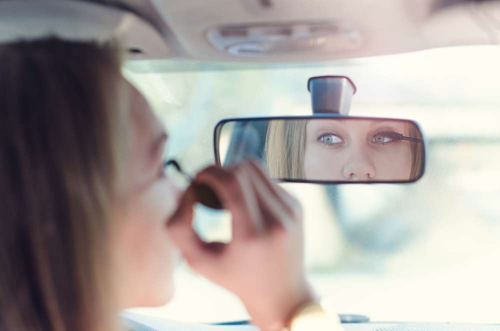 Sjåfør sminker seg bak rattet