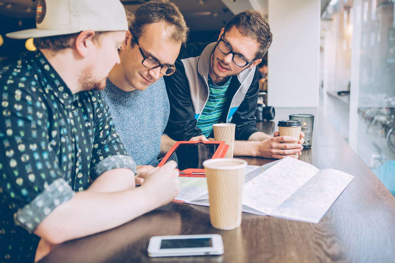 Vennegjeng med nettbrett, mobil og kart på cafe