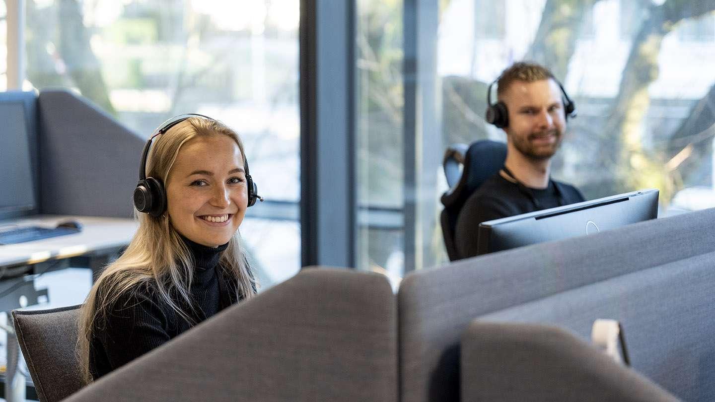 To smilende personer som jobber på Frende sitt kundesenter. Foto.