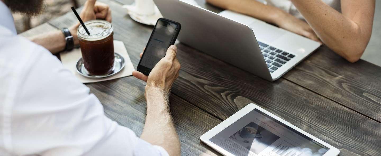 To personer med mobil, PC og nettbrett på cafe