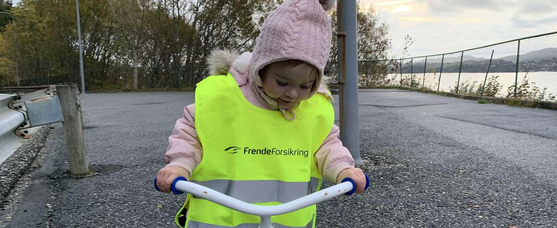 Barn på trehjulssykkel med refleks