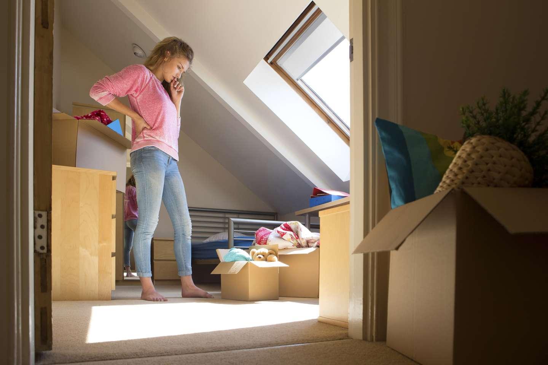 Ung kvinne pakker ut i ny leilighet