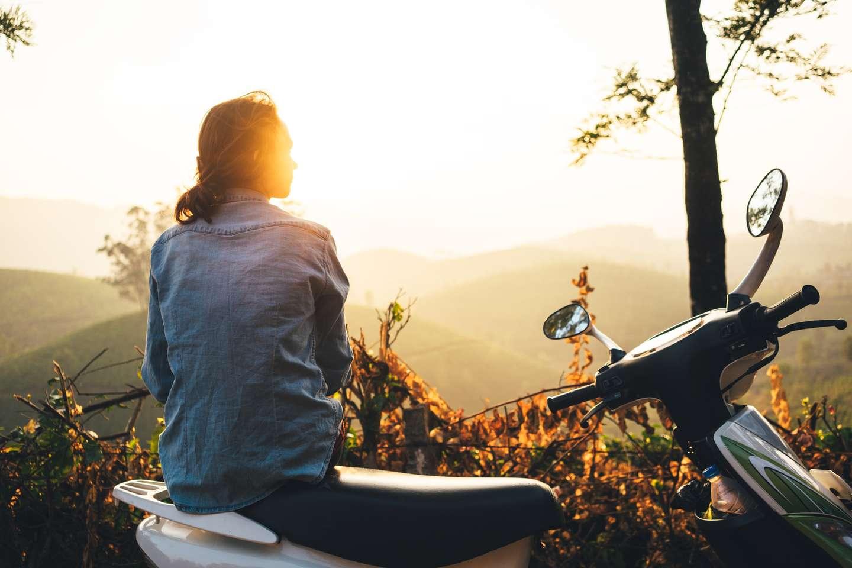 Jente med mopedforsikring i Frende skuer utover flott landskap