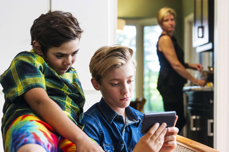 Gutter surfer på mobilen mens mor ser på fra avstand